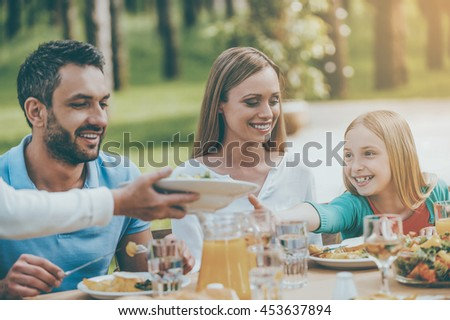 More salad please! Happy family enjoying meal together while sitting at the dining table outdoors - stock photo