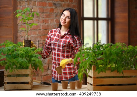 More than just existing. Shot of a cheerful smiling female brunette posing holding a tomato plant looking to the camera