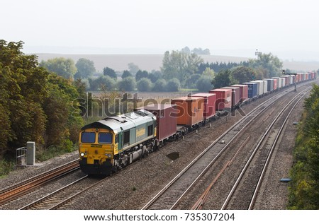 MORETON, UK - SEPTEMBER 28: A Freightliner operated intermodal train passes Moreton cutting with a full load of goods unloaded from the docks earlier in the day on September 28,2013 in Moreton