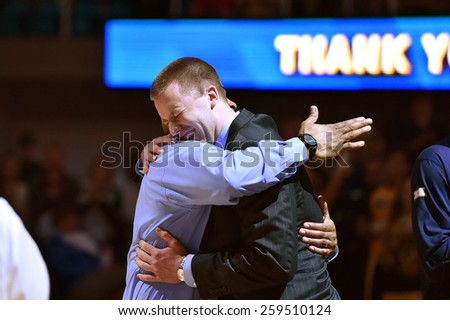 MORGANTOWN, WV - MARCH 7: WVU forward Kevin Noreen (34) is greeted by an assistant coach on Senior Night prior to the Big 12 Conference college basketball game March 7, 2015 in Morgantown, WV.  - stock photo
