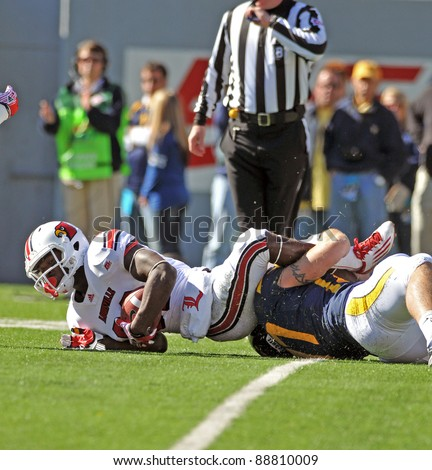 MORGANTOWN, WV - NOVEMBER 5: Louisville receiver Eli Rogers (white) is tackled after fielding a kick in the Big East football game against WVU November 5, 2011 in Morgantown, WV - stock photo
