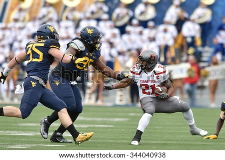 MORGANTOWN, WV - NOVEMBER 7: Texas Tech Red Raiders running back DeAndre Washington (21) tries to cut back to avoid tacklers during the NCAA football game November 7, 2015 in Morgantown, WV.  - stock photo
