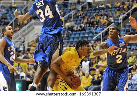 MORGANTOWN, WV - NOVEMBER 23: West Virginia Mountaineers guard Tyrone Hughes (23) gets a defender airborne in the Cancun Challenge basketball game being played November 23, 2013 in Morgantown, WV.