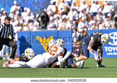 MORGANTOWN, WV - NOVEMBER 14: West Virginia Mountaineers linebacker Jared Barber (42) scoops up a fumble during the football game November 14, 2015 in Morgantown, WV.  - stock photo