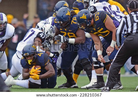 MORGANTOWN, WV - November 1: West Virginia Mountaineers running back Wendell Smallwood (4) fights for extra yardage on a carry during the Big 12 football game November 1, 2014 in Morgantown, WV.