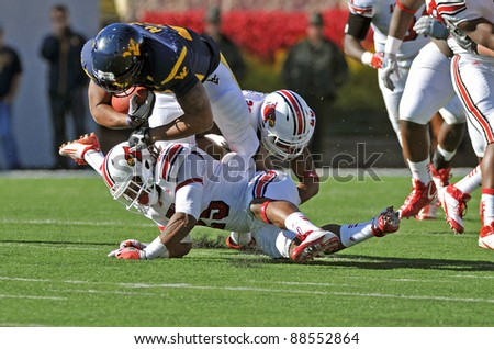 MORGANTOWN, WV - NOVEMBER 5: West Virginia running back Shawne Alston (#20) runs over two defenders during the football game between Louisville and WVU November 5, 2011 in Morgantown, WV.