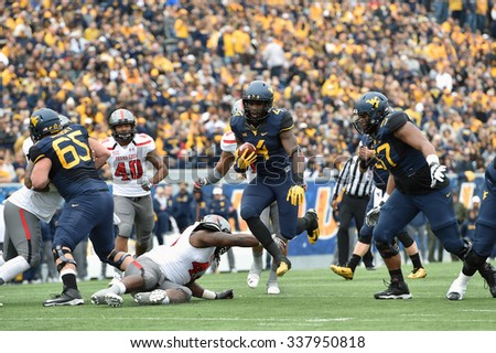 MORGANTOWN, WV - NOVEMBER 7: West Virginia running back Wendell Smallwood (4) hurdles a defender near the line on a running play during the football game November 7, 2015 in Morgantown, WV. - stock photo