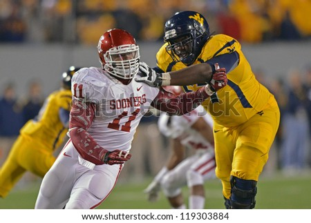 MORGANTOWN, WV - NOVEMBER 17: WVU offensive linesman Quinton Spain (67) blocks an OU defender during the Big 12 conference game between the Mountaineers and Sooners November 17, 2012 in Morgantown, WV