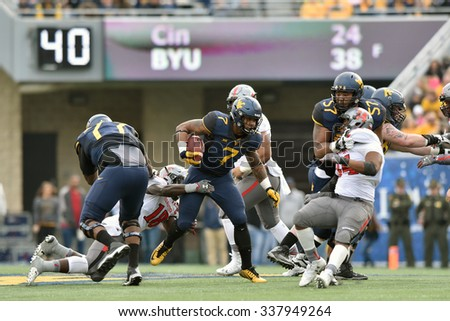 MORGANTOWN, WV - NOVEMBER 7: WVU running back Rushel Shell (7) tries to break a tackle on a rushing play during the football game November 7, 2015 in Morgantown, WV. - stock photo