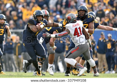 MORGANTOWN, WV - NOVEMBER 7: WVU running back Rushel Shell (7) tries to stiff arm a defender on a rushing play during the football game November 7, 2015 in Morgantown, WV. - stock photo