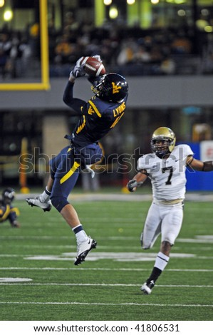 MORGANTOWN, WV - NOVEMBER 27: WVU wide receiver Wes Lyons (#4 with ball) makes an acrobatic catch in the November 27, 2009 game in Morgantown, WV. WVU upset Pitt 16-13. - stock photo