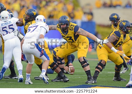 MORGANTOWN, WV - OCTOBER 4: West Virginia Mountaineers offensive lineman Michael Calicchio (63) blocks on a kick during the Big 12 football game October 4, 2014 in Morgantown, WV.  - stock photo