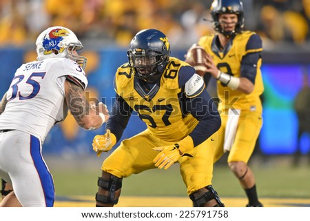 MORGANTOWN, WV - OCTOBER 4: West Virginia Mountaineers offensive lineman Quinton Spain (67) drops into pass protection during the Big 12 football game October 4, 2014 in Morgantown, WV.  - stock photo