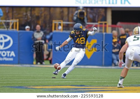 MORGANTOWN, WV - OCTOBER 18: West Virginia Mountaineers place kicker Michael Molinari (48) kicks off following a Mountaineer score during the Big 12 football game October 18, 2014 in Morgantown, WV.  - stock photo