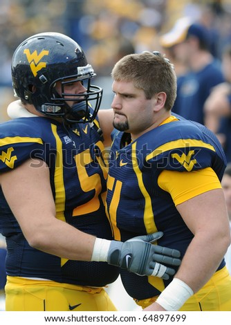 MORGANTOWN, WV - OCTOBER 23: West Virginia University offensive lineman Eric Jobe (right) gets a last good luck wish from a teammate on October 23, 2010 in Morgantown, West Virginia. - stock photo