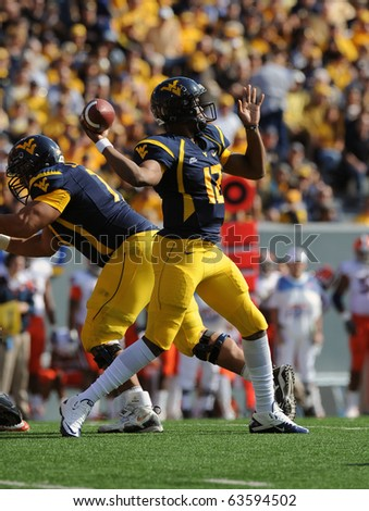 MORGANTOWN, WV - OCTOBER 23: West Virginia University quarterback Geno Smith throws a pass in the game against Syracuse October 23, 2010 in Morgantown, WV. - stock photo