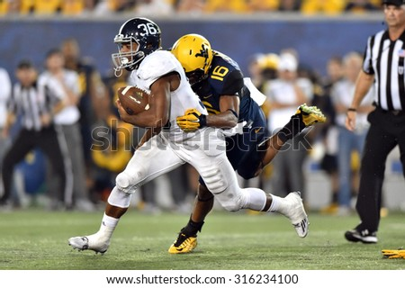 MORGANTOWN, WV - SEPTEMBER 5: West Virginia Mountaineers safety Terrell Chestnut brings down a ball carrier during the season opening game September 5, 2015 in Morgantown, WV.  - stock photo