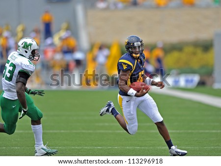 MORGANTOWN, WV - SEPTEMBER 1: WVU QB Geno Smith (w/ ball) cuts back near the sideline on a scramble during the first football game of the season against Marshall September 1, 2012 in Morgantown, WV.