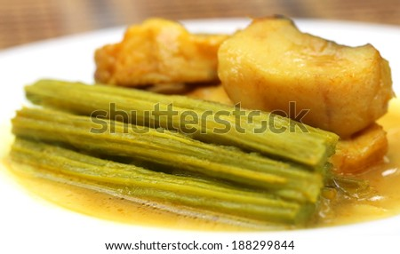 Moringa curry with fish on a plate - stock photo