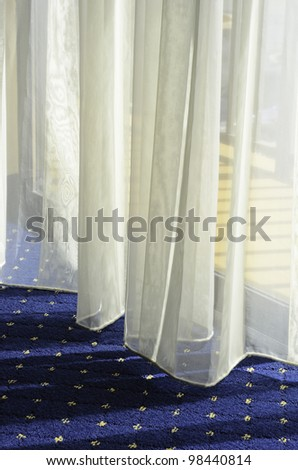 Morning at a glance: Bottom of sheer drapes almost touching carpet by glass door to hotel balcony - stock photo