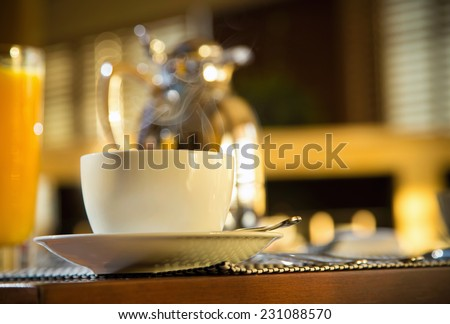 Morning at Coffee Shop in hotel with smoking hot mug. Decanter and orange juice very blurred. See more - stock photo
