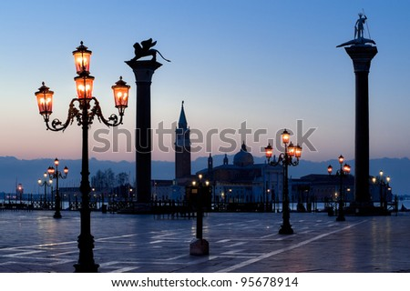 Morning at San Marco square. Saint Theodore and Lion of Saint Mark columns, and famous Venetian street-lamps. Church of San Giorgio Maggiore at the background.