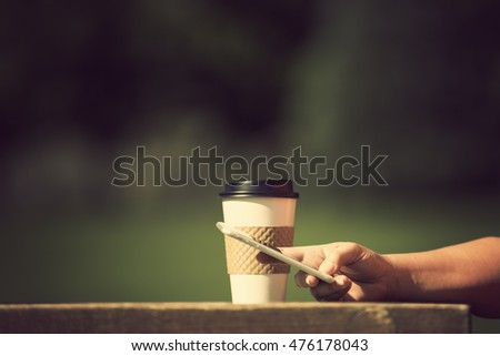 Morning at the park with take away coffee and cell phone