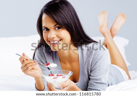 morning breakfast meal woman eating healthy yoghurt and fruit in bed while happy and smiling isolated on grey background - stock photo