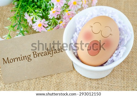 Morning breakfast tag. Eggs sleep with Expression Face in white cup and flower on sack background. - stock photo