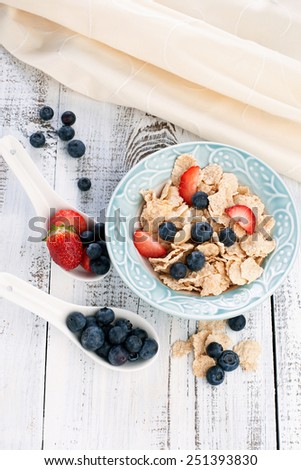 Morning breakfast with cornflakes and fresh berries on white wooden table - stock photo