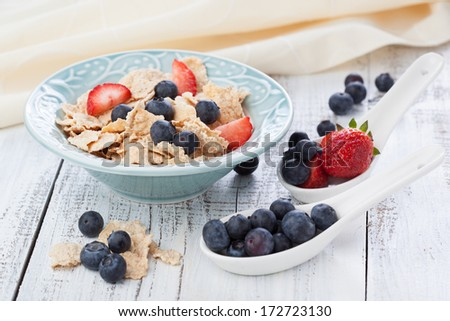 Morning breakfast with cornflakes, milk and fresh berries on white wooden table - stock photo