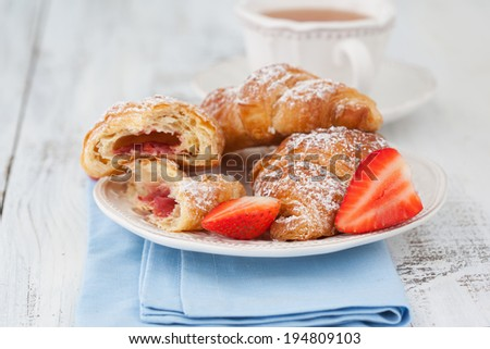 Morning breakfast with fresh croissants and cup of tea on white wooden table