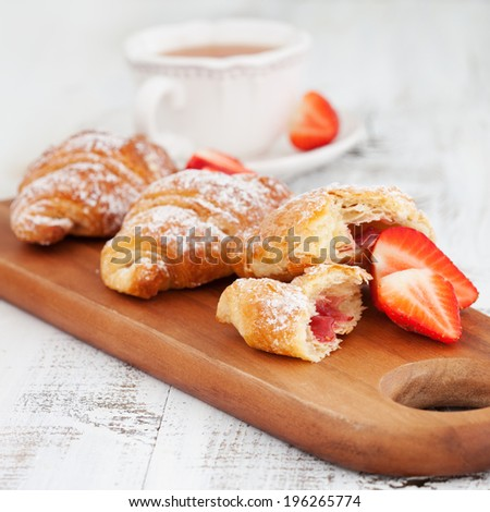 Morning breakfast with fresh croissants and cup of tea on white wooden table, selective focus