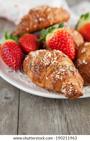 Morning breakfast with fresh croissants and strawberries on old wooden table, selective focus