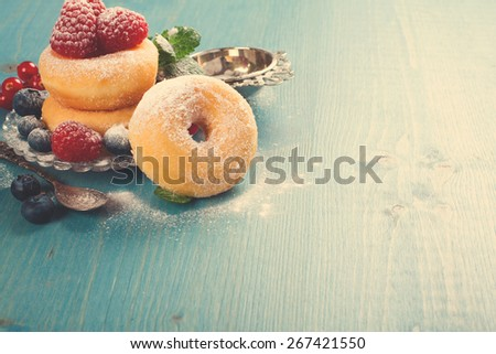 Morning breakfast with mini donuts and berries on plate under powdered sugar on blue wooden background.  Tasty donuts closeup. Doughnut. Copy space. Retro style toned. - stock photo