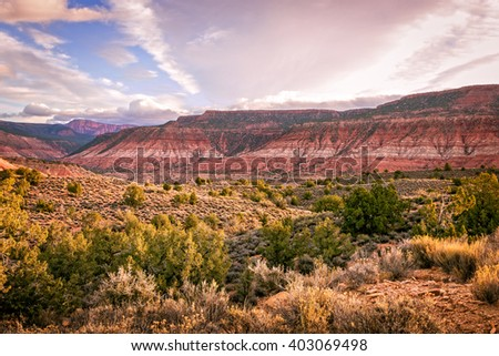 Morning breaks over the high desert plateau in southeastern Utah with colorful red and white banded geological features, scrub brush, and cloudy and blue skies