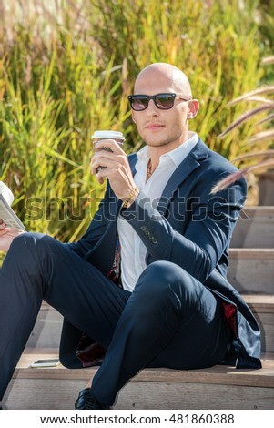 Morning business. Confident businessman sitting on the stairs holding a newspaper. Businessman drinking coffee and looking at the camera