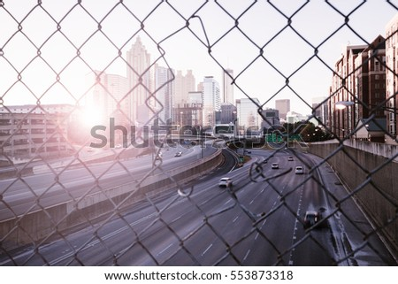 Morning city skyline through the wire mesh fence. Sunrise Atlanta cityscape, Georgia, USA