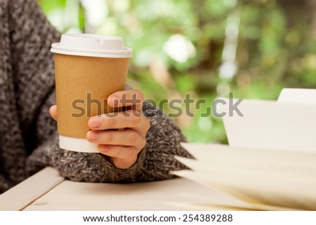 Morning coffee and a book. Woman holds a disposable coffee cup while reading a book - stock photo