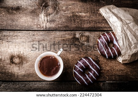 Morning - Coffee and homemade donuts filled with chocolate, a bag of donuts on a wooden table - stock photo