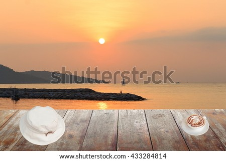 Morning coffee and White hat on wood table at sunset or sunrise sea, The delicious aroma Cappuccino coffee : space for text  and may be used as background : - stock photo