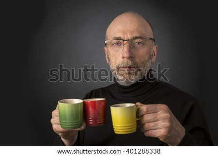 Morning coffee anybody? 60 years old  bald man with a beard and glasses carrying three espresso coffee cups - a headshot against a black background - stock photo