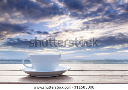 Morning coffee cup with beautiful blue sky and puffy clouds background - stock photo