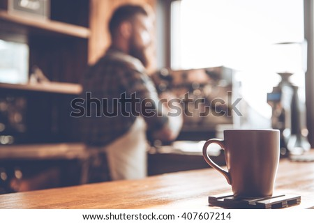 Morning coffee. Focused picture of coffee cup standing at bar counter with young bearded man in apron making coffee in background - stock photo