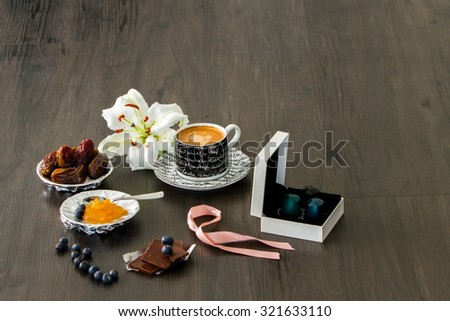 Morning coffee setting with coffee gift box, pink ribbon, dry dates, orange marmalade, blueberries and white lily flower - stock photo