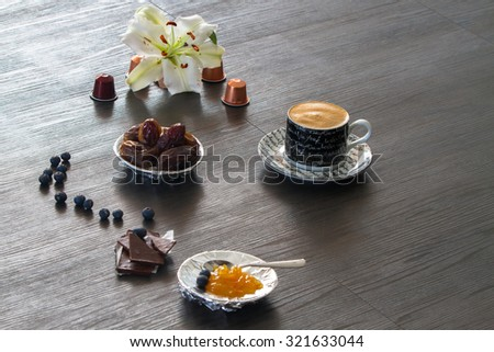 Morning coffee setting with dry dates, orange marmelade, blueberries and white lily - stock photo