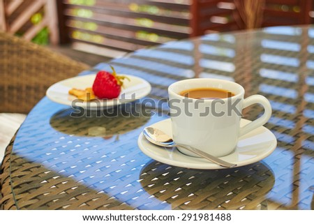 morning coffee with strawberries on a table on the terrace, dessert, aura - stock photo
