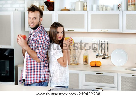 Morning coffee. Young and beautiful couple are holding a cup of coffee and drink until their backs to each other in the kitchen and smiling directly at the camera. - stock photo