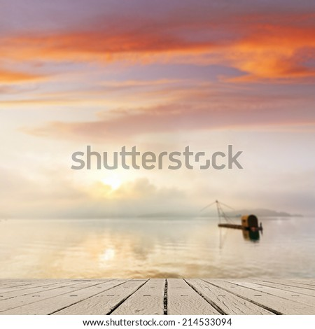 Morning concept with boat on lake with sunlight and dramatic sky, focus on wooden desk. - stock photo