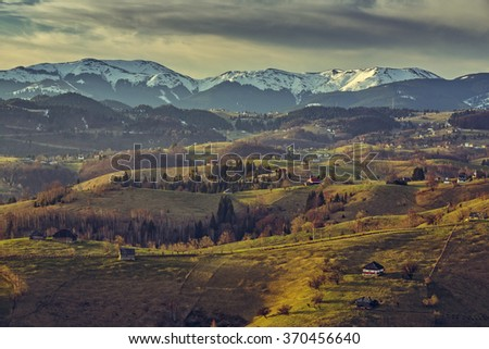 Morning countryside landscape with traditional Romanian scattered houses in the valleys of Bucegi mountains uphill in Sirnea village, Brasov county, Romania. - stock photo